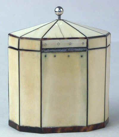 Hygra: A ten sided tortoiseshell strung ivory  tea caddy with a pyramid top  having a silver ball finial,   a silver escutcheon, and silver plaque on the front encircled with pique point. Circa 1790.