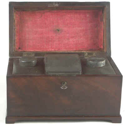 A flame mahogany tea chest of traditional Chippendale form with cavetto molding to the top and edged subtly with rope twist banding having brass edge escutcheon and Dutch drop handle and containing three tinned ferrous metal lift out containers. Circa 1775. mahchcan02.jpg (35202 bytes)