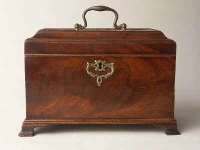 A flame mahogany tea chest of traditional Chippendale form having fretted brass escutcheon and top carrying handle with a sliding side revealing a secret spoon drawer and standing on bracket feet. Circa 1770