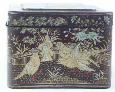 A Chinese export lacquer tea caddy in reddish earth colored lacquer having rounded corners decorated with two colors of gold depicting groups of birds highlighted in red lacquer. Circa 1840