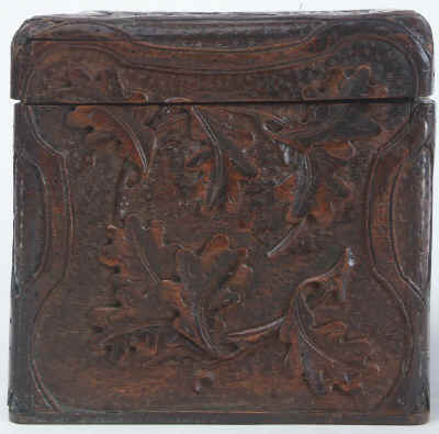 A tea caddy of cube form with the top and sides deeply carved depicting trailing oak leaves