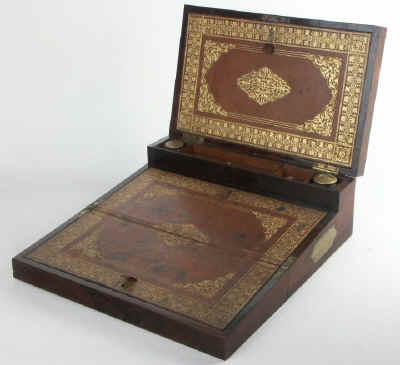 A very fine brass bound triple opening writing box with secret drawers, made by one of the most eminent  makers of the Regency period. The box is marked 'Bayley's' 17. Cockspur St. ' follow Link. Rosewood crossbanded with ebony inlaid with separate brass elements having 'lucky' quatrefoil centers. The quality screams.