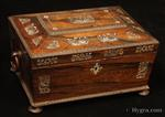 JB675: Antique box in the sarcophagus form. The box is veneered in figured rosewood and is inlaid in mother of pearl depicting stylized flora with birds. The fluid design of stylised flora is exceptionally fine. This is a spectacular box which encapsulates the best of the Regency era. The box stands on turned rosewood feet and has turned rosewood drop ring handles. The centre panel of the top is framed with gadrooning as is the pediment adding the architectural impact. The box has a lift out tray which has been relined. Circa 1825. . more details