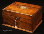 JB678: Figured walnut box with a drawer concealed behind a hinged door, opening to a fitted plush interior with lift-out tray fitted for jewelry. The box has rounded ebony edges and a countersunk carrying handle to the top. Circa 1890.
