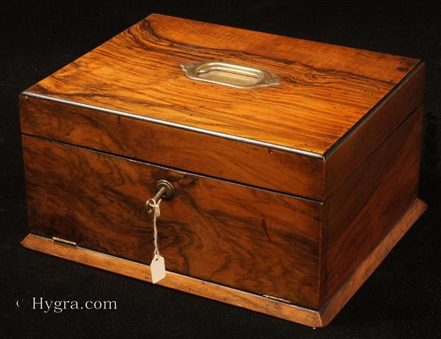 Figured walnut box with a drawer concealed behind a hinged door, opening to a fitted plush interior with lift-out tray fitted for jewelry. The box has rounded ebony edges and a countersunk carrying handle to the top. Circa 1890.  Enlarge Picture