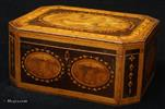 740SB: A very rare octagonal Georgian sewing box in harewood with crossbandings in various woods, ovals in burr yew, kingwood and book matched burr wood and inlays of fine leaves and dots. The top is decorated with a hand coloured print of a classical scene and framed in shaded maple, in the form of inlaid rippled ribbon. The whole orchestration of the decoration is rooted in the neoclassical tradition of the late 18th-early19th century and it is one of the finest examples of the genre. The interior contains a wealth of finely turned original sewing tools in the original tray and pieces of its two hundred year old sewing history. This box is an early example of Tunbridge ware, when the work made in the area was more in keeping with the general taste of the country and not particular to the area. There are however pointers to the work specific to the area, such as the subtle use of particularly beautiful small pieces of wood, finely turned wooden tools, the inlay of pointed leaves and dots and the painting of lines on turned pieces. The paper is also typical, although not exclusive to Tunbridge ware boxes.   Circa 1800.