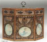 TC110: A late 18th century rolled paper tea caddy the framed panels of filigree spaced ornament on a background of mica flakes and having colored prints of classical inspiration under glass. The caddy is framed with fruitwood inlaid with a chevron of dark and light wood. Circa 1800.