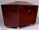 TC121: A flame mahogany tea caddy of tapered pyramid shape standing on brass ball feet with two lidded compartments and a central place for sugar bowl circa 1820.