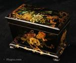 711TC: Papier mâché two compartment tea caddy the japanned surface decorated with naturalistic paintings of flowers; The design is artfully orchestrated. Rococo trellised flora both frames and intersects the naturalistic  rendition of the frames and intersects the naturalistic rendition  of the the flowers and bird in a fluid cartouche. This is executed in gold leaf and provides a glamorous and exotic highlight against the subtlety  of the realistic colour of the main pictures. Circa: 1850.