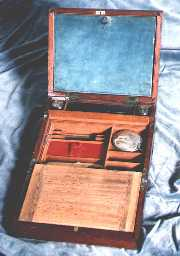 A combined writing box and dressing box of c1800. The top writing flap opens down to give access to grooming/shaving accessories. The lower flap has the conventional space for storing paper. The box is typical of the period made with solid mahogany reinforced with brass bindings. The brass binding protects the box from warping in changes of humidity. It also provides structural reinforcement for something expected to have a hard and useful life.        �
