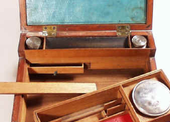 When the tray is lifted, the back panel under the pen tray slides up to reveal two secret drawers.