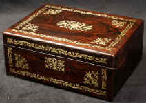 JB506:  Rosewood box  with rounded edges, inlaid with brass to the front and top depicting stylized flora.  The design is controlled in deference to the Georgian neo-classical tradition but it also embraces the Regency influence of the Royal cabinet maker George Bullock, who introduced naturalistic elements to the earlier austere brass designs.  The inside of the box has been relined with hand marbled paper and velvet  and retains  its original lift out tray.  Circa 1825.  Enlarge Picture