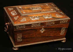 -Antique box in the sarcophagus form. The box is veneered in figured rosewood and is inlaid in mother of pearl depicting stylized flora with birds. The fluid design of stylised flora is exceptionally fine. This is a spectacular box which encapsulates the best of the Regency era. The box stands on turned rosewood feet and has turned rosewood drop ring handles. The centre panel of the top is framed with gadrooning as is the pediment adding the architectural impact. The box has a lift out tray which has been relined . Circa1825. -Enlarge Picture
