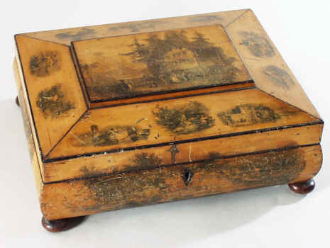 A shaped Scottish sewing box made from sycamore decorated with transfer decoration of different views.  The views are romantic visions of the countryside. The interior is partitioned for sewing tools with a lidded central compartment decorated with yet another picture. Second quarter 19th century.