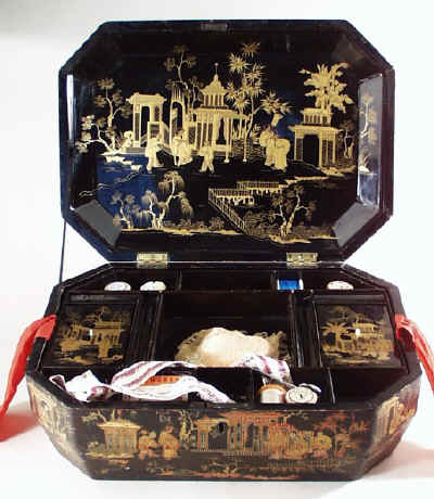 large Chinese export lacquer Chinese sewing box, decorated all over with scenes of oriental figures in gardens in raised gilded lacquer. Circa 1840.