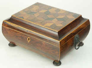 A bombe shaped box, the main body veneered in rosewood, the top in parquetry. This box is an excellent example of early nineteenth century Tunbridge ware work. During the first decades of the nineteenth century, Tunbridge ware developed a distinctive style, which utilised the beauty of the different woods, both local and imported, available to the makers working in the area of Tunbridge Wells in  Kent. By careful juxtaposition of figure, cut, colour and even peculiarity, such as a fungal attack, the artist/craftsmen, celebrated the richness of the natural world by displaying it on impeccably structured boxes. Circa 1815
