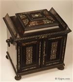 A monumental coromandel ebony compendium table cabinet of architectural form having turned and carved feet and handles. It is profusely inlaid to the top and front with mother of pearl.  The compendium is the personal space for the owner and has a fully fitted sewing tray complete with its original filigree silver and bone thread spools and other tools, There are two drawers for jewelry, and a folding writing box.