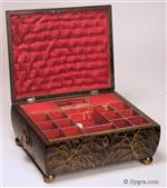 638SB: Delightful Regency fitted sewing box decorated with erudite Chinoiserie images  opening to a  compartmentalized lift out tray .  The  artist who painted the box seems to have an understanding of the symbolism and  style of Chinese Export lacquer. On the  convex sides are depictions of feathery willows. The raised painting on the top depicts figures in a garden. The  box has embossed gilded pressed brass drop ring handles and ball feet.  These are typical of the Regency , Circa 1815.