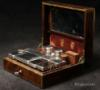 JB601: Fine brass bound  rosewood  N�CESSAIRE DE VOYAGE by L. Aucoc Ain�, Paris, with small Bramah type lock, the tightly packed compartmentalized interior lined with earth red shagreen leather and velvet and having silver topped cut crystal bottles and boxes. Circa 1840.