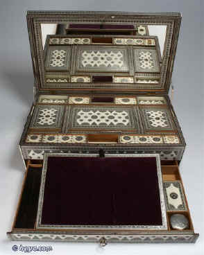 Important large Anglo Indian fully fitted sewing and writing box of pyramided shape veneered with ivory profusely inlaid with sadeli mosaic, the box having swan neck handles to the sides and standing on cast paw feet of unusual design. Inside the box is compartmentalized and fitted for sewing, with fragrant sandalwood and has supplementary lids and trays each veneered with ivory inlaid with sadeli,  circa 1845.  Enlarge Picture
