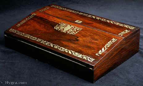WB463: Writing slope in rosewood with brass inlay circa 1820. It is veneered in saw cut rosewood on mahogany and it is inlaid in brass.Inside the box has lidded compartments for pens, wax etc and two screw top distinctive inkwells. Enlarge Picture