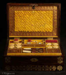 SB524: Rosewood and brass inlaid sewing box in high Regency style circa 1815. A box veneered in beautifully figured rosewood and inlaid with brass. The design of the inlay is of highly stylized flora, suggesting neoclassical designs hinting at trefoil motifs. The juxtaposition of dark wood with bold brass inlay was popular in the early part of the 19th century. The wood and the bright brass were mutually enhancing. The box retains its original  fully fitted tray covered in yellow paper with gold embossed supplementary lids. There is a set of  eight turned and carved vegetable ivory  spools. Enlarge Picture
