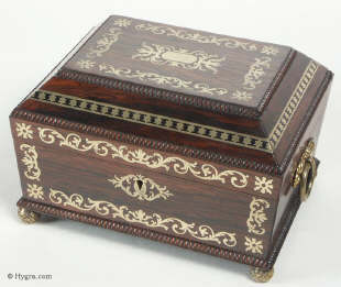 A fully fitted brass inlaid rosewood sewing box with gadrooned edges gilt side carrying handles and gilt feet. Inside the fully fitted sewing tray contains a set of turned ivory spools.  Circa 1810. Enlarge Picture