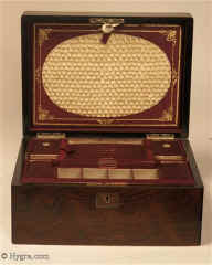 Ref: 637SB: Fitted figured rosewood sewing box with lift-out tray. The box is in very good original condition. There is a document wallet in the lid.  The front of the document wallet is covered with ruched  satin silk and framed by wine colored silk with gilded embossing. The tray retains its original supplementary lids with places designed to hold sewing tools. Circa 1850.   Enlarge Picture