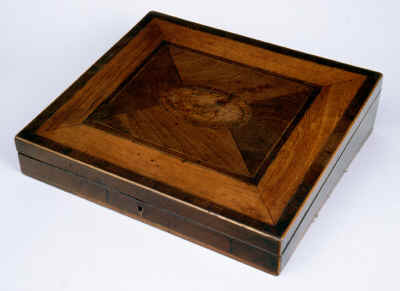 A writing slope veneered in mahogany. The whole top is framed in pear wood. The center with an oval of burr yew, crossbanded in mahogany. A symmetrical effect in the neoclassical tradition is achieved by the juxtaposition of timbers, grain, and figure. A subtle piece of inspired craftsmanship, the design belies the complexity of the work. Typical of the school of understated quality of the Georgian period.